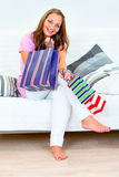 Laughing woman sitting on divan with shopping bags Stock Photography