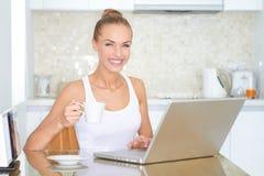 Laughing woman sitting at laptop computer Royalty Free Stock Image
