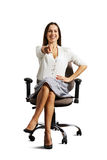 Laughing woman sitting on the office chair. And pointing at camera. isolated on white background Royalty Free Stock Photo