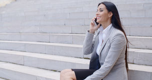 Laughing woman sitting on steps with phone Royalty Free Stock Images