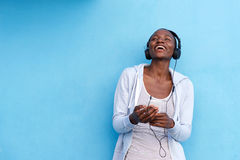 Laughing woman with smart phone and headphones by blue wall Royalty Free Stock Images