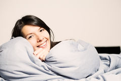 Laughing woman snuggling up in her bed Stock Image