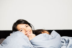 Laughing woman snuggling up in her bed Royalty Free Stock Photography