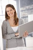 Laughing woman standing with laptop in hand Royalty Free Stock Photography