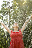 Laughing woman standing under a spray of water Royalty Free Stock Photo