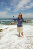 Laughing woman stands in sea-wave foam Stock Photos