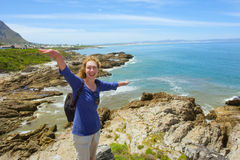Laughing woman stands on steep rock Stock Photo