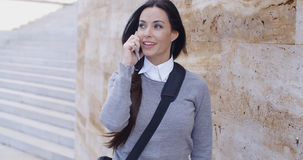 Laughing woman in sweater near wall on phone Stock Photo