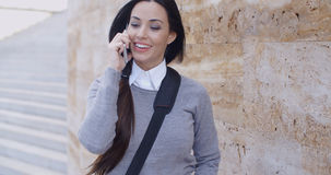 Laughing woman in sweater near wall on phone Royalty Free Stock Photography