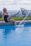 Laughing woman at swim pool. Attractive blond woman laughing while sitting on swimming pool edge splashing water with her foot Stock Image