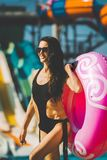 Laughing woman with swim ring near pool and slides. Beautiful laughing woman with slim figure in black bikini holding a swim ring standing near the swimming pool stock photos