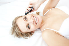 Laughing woman talking on phone lying on her bed Stock Photo