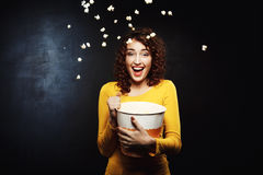 Laughing woman throwing up popcorn up in the air. Looking straight. Happy emotions. Fun time Stock Image