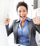 Laughing woman thumbs up. Laughing business woman thumbs up at workplace Stock Image