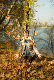 Laughing woman tossing leaves Royalty Free Stock Photo