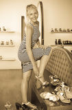Laughing woman trying on pair of sandals royalty free stock image