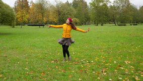 Laughing woman turning around and dancing in autumn leaves. Celebrating holidays and enjoy fall concept stock video footage