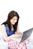 Laughing woman using a laptop sitting on bed Royalty Free Stock Image