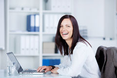Laughing woman using a laptop Stock Image