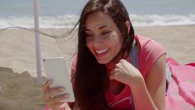 Laughing woman using phone at beach. Single laughing woman in pink using phone at beach with wind blowing through her long brown hair stock video footage