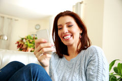 Laughing woman using smartphone Stock Photos