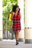 Laughing woman walking with shopping bags and mobile phone Royalty Free Stock Photos