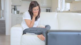 Laughing woman watching television stock video footage