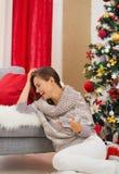 Laughing woman watching TV near Christmas tree Royalty Free Stock Image