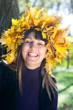 Laughing woman wearing autumn leaves Royalty Free Stock Images
