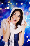 Laughing woman in white knitted scarf on blue snowflake background. Royalty Free Stock Image