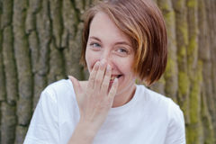 Laughing woman in white shirt with red hair over tree. She closes her mouth and smile Stock Image