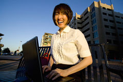 Laughing Woman Works on Laptop - Horizontal Stock Photo