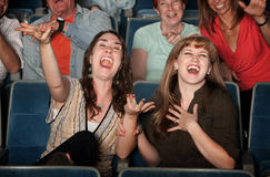 Laughing Women in Audience. Young women laugh out loud in theater Stock Images