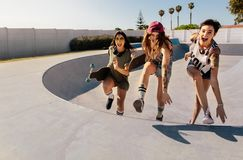 Laughing women climbing a skateboard ramp. Group of girls having a great time at skate park Stock Photos