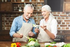 Woman cooking with husband stock photography