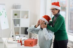 Surprise at work. Laughing women covering her co-worker eyes by hands while making Christmas surprise Royalty Free Stock Photo