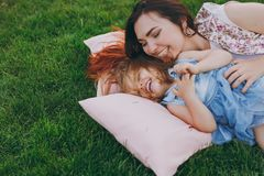 Laughing woman in light dress and little cute child baby girl lie on green grass in park rest, play and have fun. Mother. Laughing women in light dress and royalty free stock photography