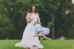 Laughing woman in light dress and little cute child baby girl playing circling around on green grass in park. Mother. Laughing women in light dress and little stock photography