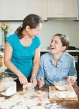 Laughing women making  pies or  meat dumplings Stock Images