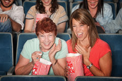 Laughing Women at Picture Show. Two laughing women with popcorn bags at a picture show Royalty Free Stock Image
