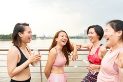Laughing women in sportswear chatting on seafront. Young smiling Asian women in sportive clothes standing together on city waterfront and chatting in leisure stock photo