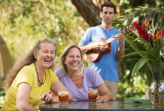 Laughing Women with Ukelele Player Stock Photos