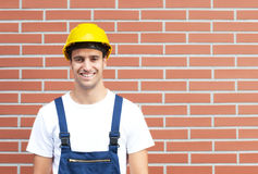 Laughing worker in front of a brick wall Stock Image