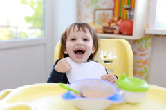 Laughing 2 years toddler eating oatmeal Royalty Free Stock Photo