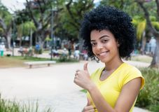 Laughing young adult woman with curly black hair showing thumb u. P outdoor in the summer in the city Royalty Free Stock Image