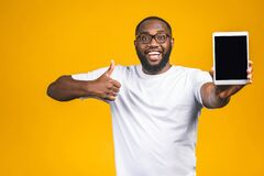 Free Laughing Young African American Man Holding A Touch Pad Tablet PC On Isolated Against Yellow Background. Thumbs Up Royalty Free Stock Photography - 185890007