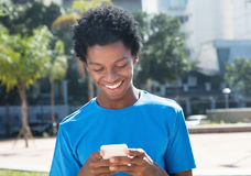 Laughing young african american man sending message with mobile. Phone outdoor in the city in the summer Stock Image