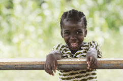 Laughing young African girl sitting in her desk. Little african girl sitting at wooden table and smiling at camera with blurred background Stock Photo