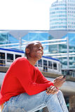 Laughing young african man sitting outside using cellphone. Side portrait of laughing young african american man sitting outside using cellphone Stock Photo