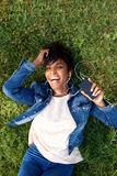 Laughing young african woman lying on grass with earphones and m Stock Images